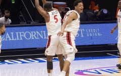 San Diego State men's basketball senior forward Matt Mitchell and freshman guard Lamont Butler left) celebrate at half court after the Aztecs' 62-58 win over Boise State on Feb. 27, 2021 at Viejas Arena.