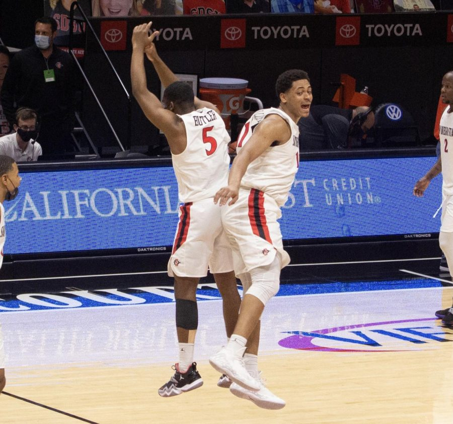 San Diego State men's basketball senior forward Matt Mitchell and freshman guard Lamont Butler (left) celebrate at half court after the Aztecs' 62-58 win over Boise State on Feb. 27, 2021 at Viejas Arena.
