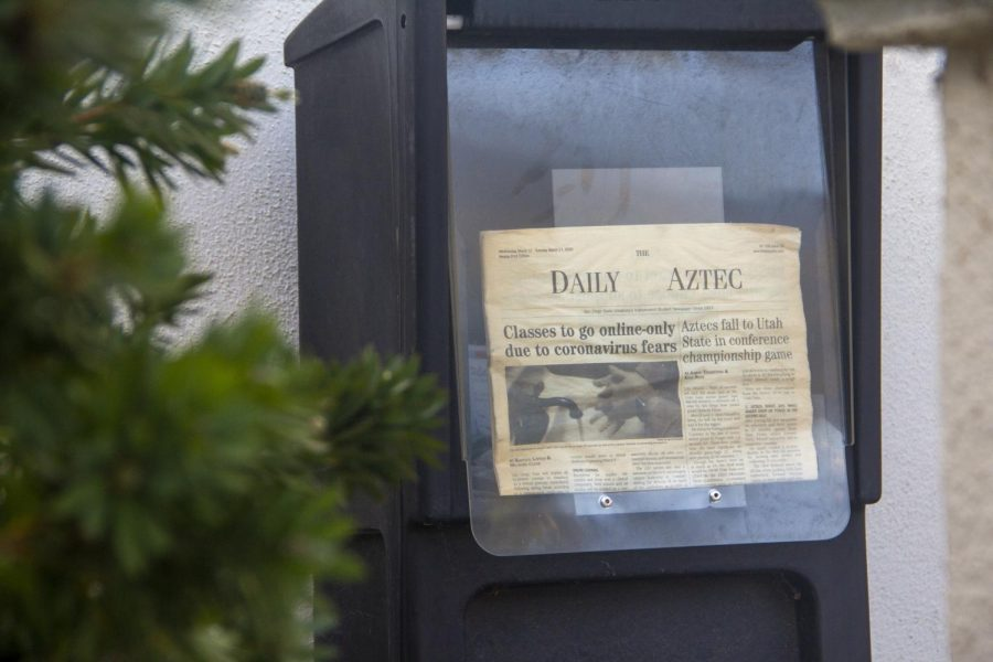 A newstand with an old, faded edition of The Daily Aztec print edition.