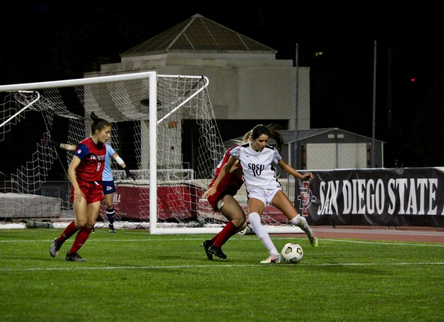 San Diego State women's soccer junior forward Anna Toohey attempts to work her way around Fresno State defenders during the Aztecs' 2-1 win over Fresno State on March 27, 2021 at the SDSU Sports Deck.