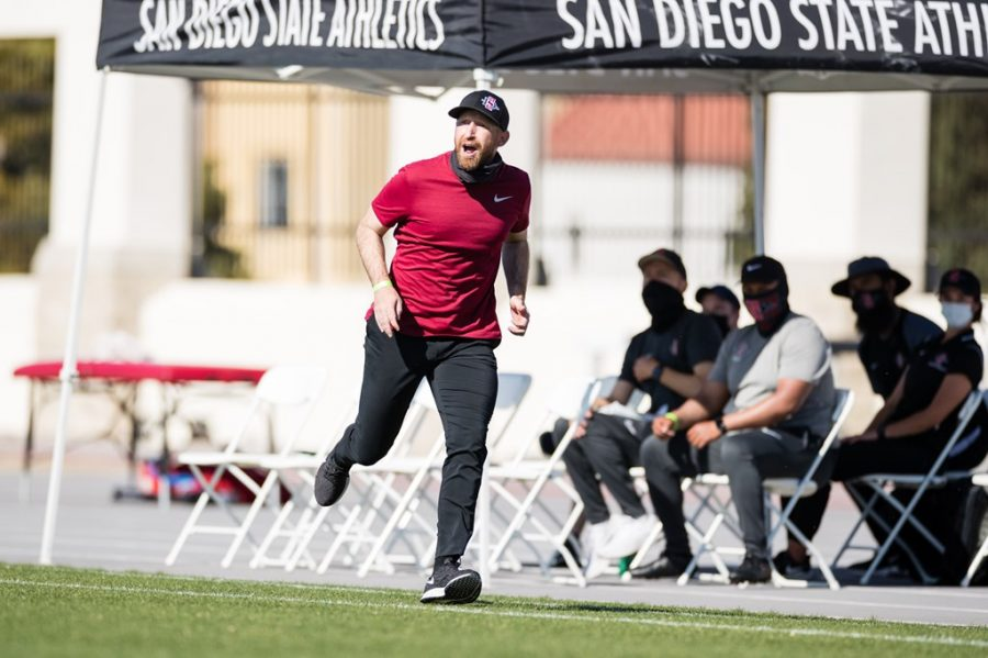 San Diego State men's soccer head coach Ryan Hopkins runs down the touchline shouting instructions at his players during the Aztecs' 2-0 upset over No. 4 Washington on March 28, 2021 at the SDSU Sports Deck.
