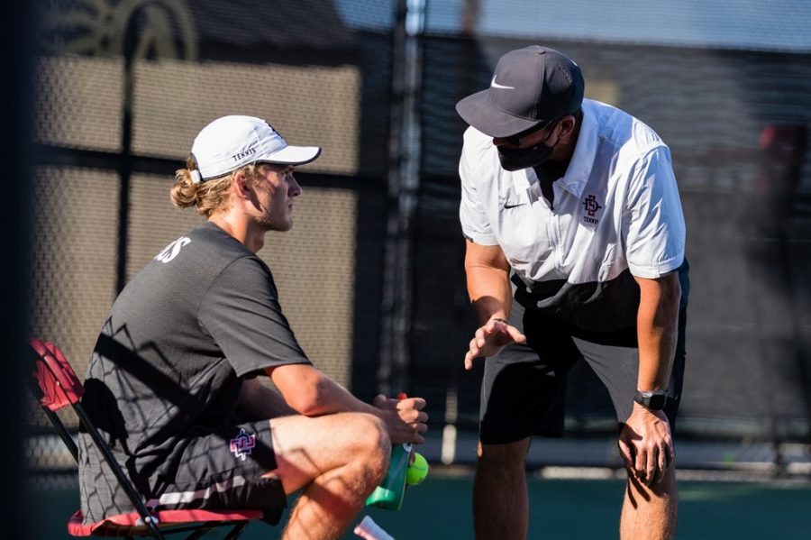 San Diego State men's tennis head coach Gene Carswell (right) talks to freshman Roni Rikkonen during the Aztecs 4-2 loss to UC Davis on March 5, 2021 at the Aztec Tennis Center.
