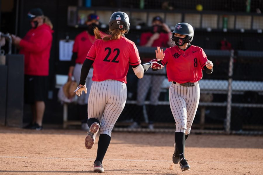 San Diego State softball junior catcher/utility player Danielle Romanello (left) high-fives freshman outfielder Eliana Reyes during the Aztecs' doubleheader versus St. Mary's on March 13, 2021 at the SDSU Softball Stadium.