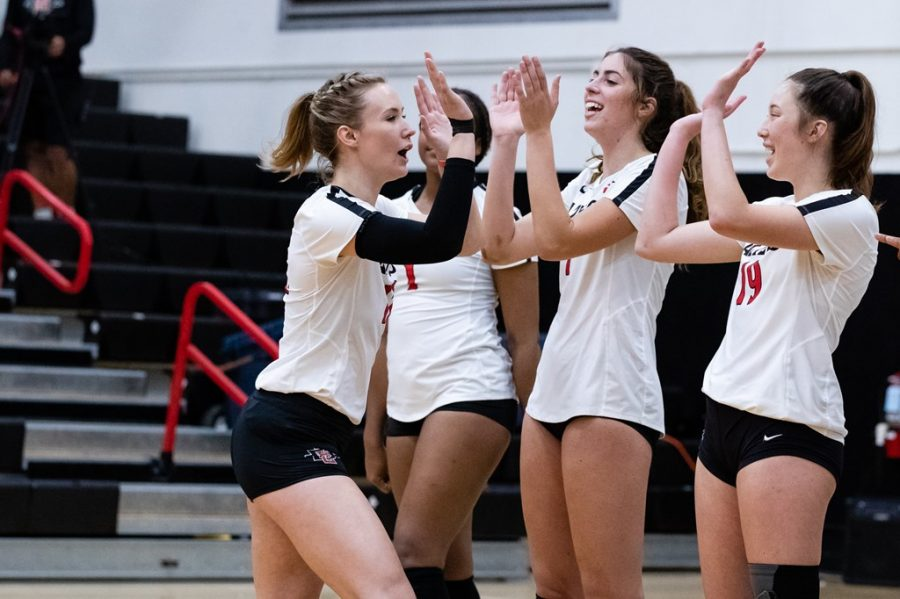 San Diego State volleyball senior middle blocker Erin Gillcrist high-fives her teammates before the Aztecs' 3-0 win over Colorado State on April 3, 2021 at Peterson Gym.