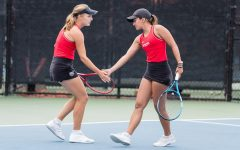 San Diego State women's tennis junior Alicia Melosch (left) high fives senior Tamara Arnold during the Aztecs' 4-0 win over Air Force on April 11, 2021 at the Aztec Tennis Center.