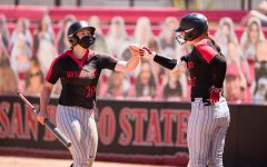 San Diego State softball senior shortstop Shelby Thompson (left) high-fives junior utility player/catcher Danielle Romanello (right) during the Aztecs' 14-3 win over San José State on April 18, 2021 at the SDSU Softball Stadium.