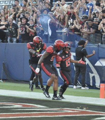 Running Back Jordyn Byrd (right) celebrates with his teammates after scoring a touchdown against Utah