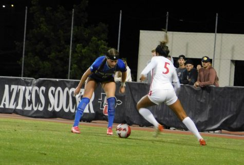 Sophomore forward Emma Gaines-Ramos (5) looking to deke around the Air Force player for a goal scoring opportunity.