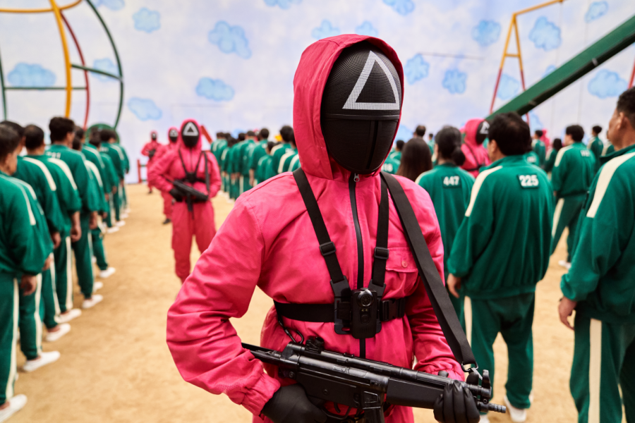 The figures in red jumpsuits oversee the games and eliminate competitors who break the rules.